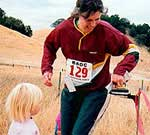 Janet punches the finish with the help of twin daughters Katie and Sarah; Morgan Territory A-meet, October 2001 (Photo: Judy Koehler)